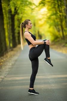 Młoda sportowa biegaczka rozgrzewa się na zewnątrz