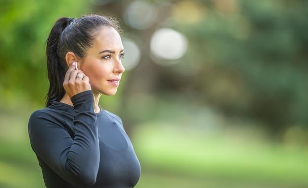 Młoda sportowa biegaczka z miłym uśmiechem przed bieganiem ze słuchawkami słucha muzyki motywacyjnej.