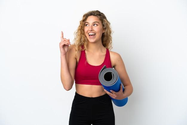 Młoda sportowa blondynka idzie na zajęcia jogi, trzymając matę na białym tle, wskazując świetny pomysł