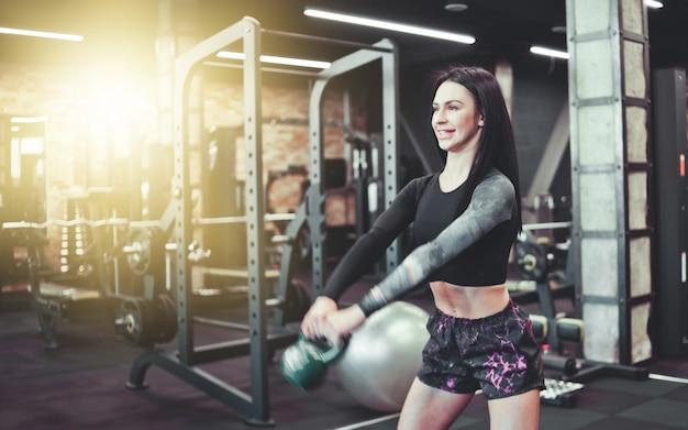 Młoda sportowa brunetka robi szarpnięcie ćwiczenia z kettlebell. na siłowni. trening siłowy z wolnymi ciężarami, trening funkcjonalny