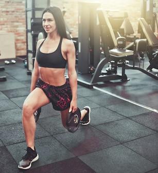 Młoda sportowa brunetka robi wypad na nogi ćwiczenia ze sztangą w rękach siłowni.