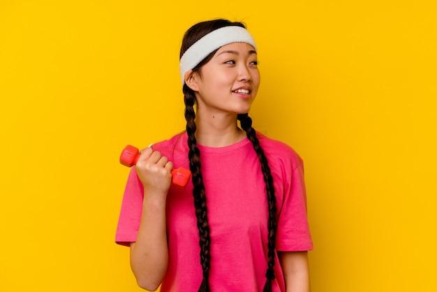 Młoda sportowa chinka na żółtym tle wygląda z boku uśmiechnięta, wesoła i przyjemna.