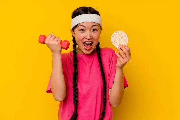 Młoda sportowa chińska kobieta je ciastka ryżowe na żółtym tle
