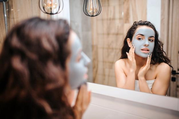 Młoda sportowa ciemnowłosa piękna kobieta robi rutyny wieczorem rutyny w lustrze. ma kremową maskę na twarzy i dotyka go rękami. spokojnie i pokojowo.