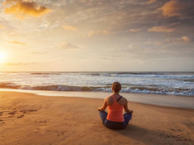 Młoda sportowa dysponowana kobieta robi joga oudoors przy plażą