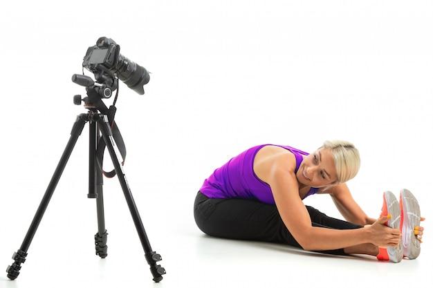 Młoda sportowa dziewczyna o jasnych włosach siedzi przed kamerą i pokazuje, jak ćwiczyć