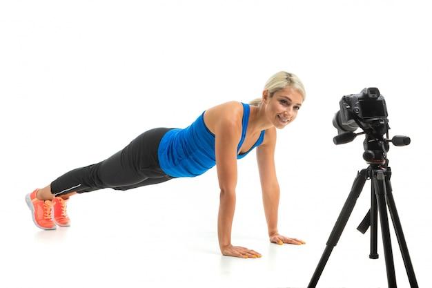 Młoda sportowa dziewczyna o jasnych włosach siedzi przed kamerą i pokazuje, jak robić deski