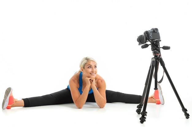 Młoda sportowa dziewczyna o jasnych włosach siedzi przed kamerą i pokazuje, jak robić sznurek