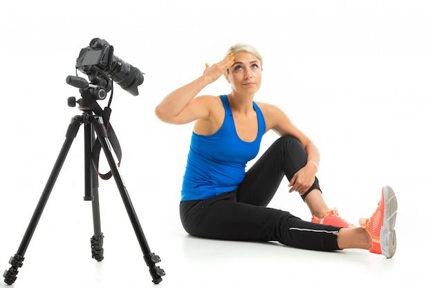 Młoda sportowa dziewczyna o jasnych włosach siedzi przed kamerą, pokazuje, jak ćwiczyć i jest zmęczona