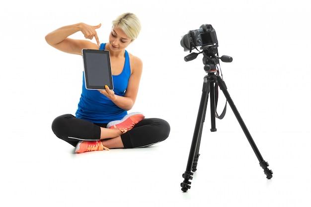 Młoda sportowa dziewczyna o jasnych włosach w czarnym temacie sportowym, czarnych leginsach i jasnych tenisówkach pokazuje smartfona przed kamerą.