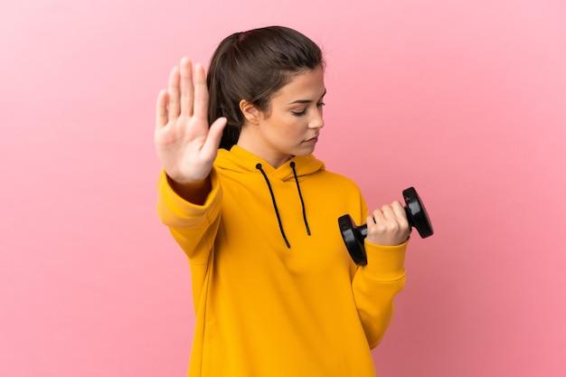 Młoda sportowa dziewczyna robi podnoszenie ciężarów na białym tle różowym tle robi gest stop i rozczarowana
