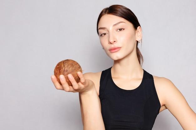 Młoda sportowa dziewczyna trzyma kokos