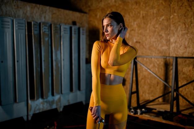 Młoda sportowa dziewczyna w żółtym sportowym mundurze przygotowuje się do treningu nowoczesnej siłowni w stylu loft