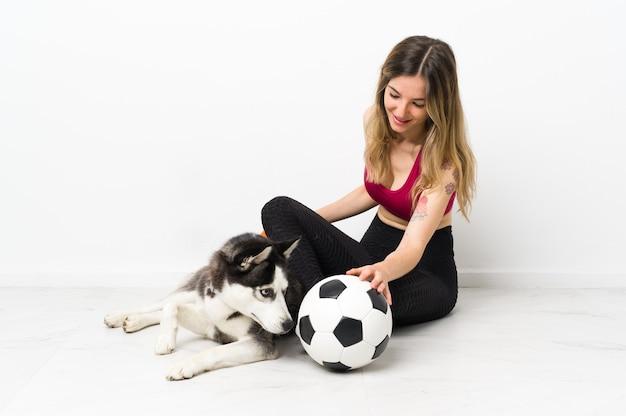 Młoda sportowa dziewczyna z psem siedzi na podłodze