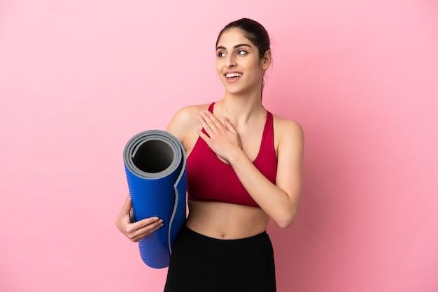 Młoda sportowa kaukaska kobieta idzie na zajęcia jogi, trzymając matę, patrząc w górę, uśmiechając się