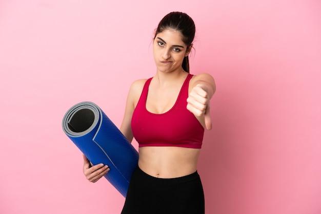Młoda sportowa kaukaska kobieta idzie na zajęcia jogi, trzymając matę pokazującą kciuk w dół z negatywnym wyrazem twarzy