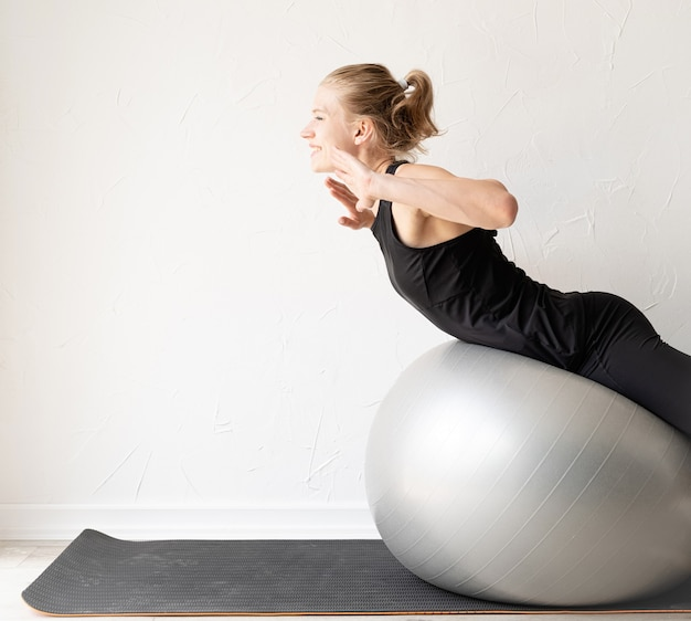 Młoda sportowa kobieta ćwicząca na piłce fitness