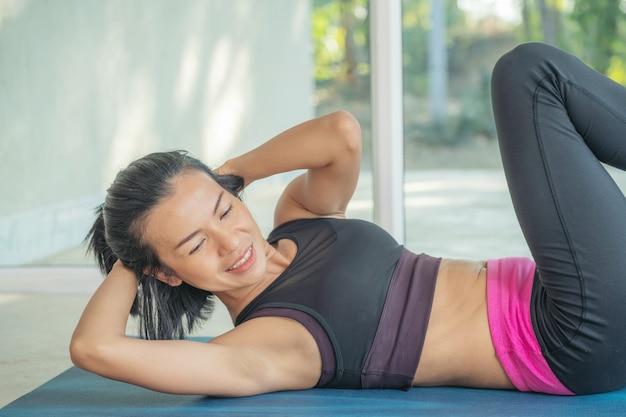 Młoda sportowa kobieta ćwiczy, wykonuje ćwiczenia krzyżowe, brzuszki rowerowe, ćwiczy, nosi odzież sportową, ogląda samouczek wideo fitness online na laptopie, ćwiczy w domu siedząc.
