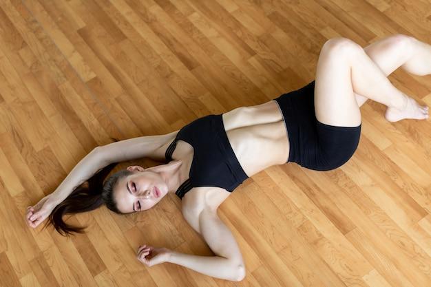 Młoda sportowa kobieta ćwiczy, wykonuje ćwiczenia krzyżowe, pozuje brzuszki rowerowe, ćwiczy, nosi odzież sportową, czarne spodnie i top, kryty na całej długości.