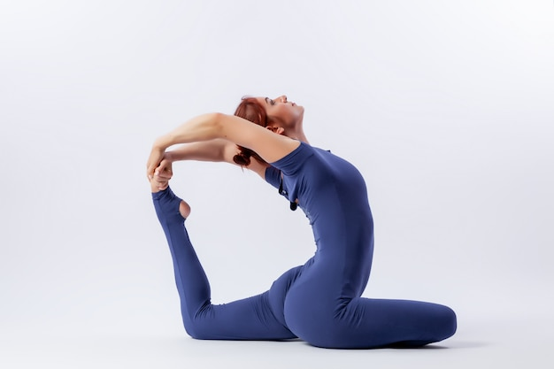 Młoda sportowa kobieta gimnastyczka w gimnastycznym kombinezonie robi rozciąganie w trudnej pozie