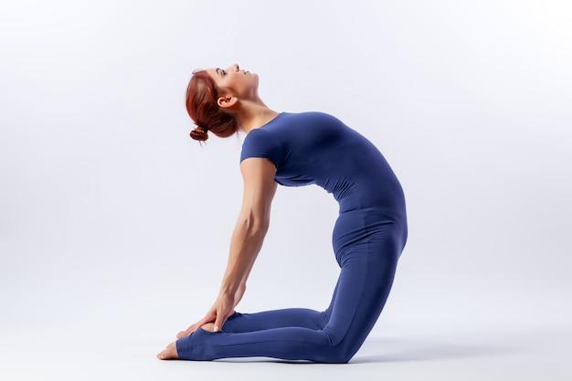 Młoda sportowa kobieta gimnastyczka w gimnastycznym kombinezonie robi rozciąganie w trudnych pozach