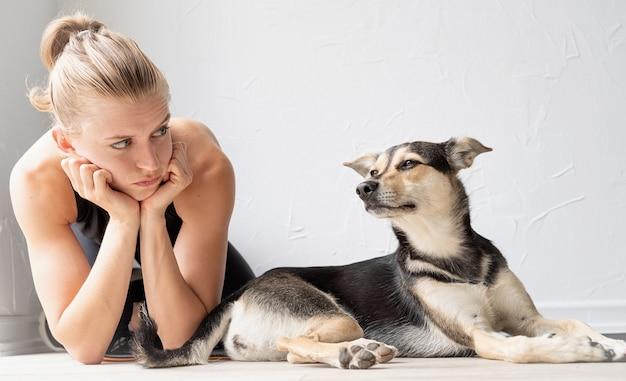 Młoda sportowa kobieta leżąca na podłodze patrząca na swojego psa