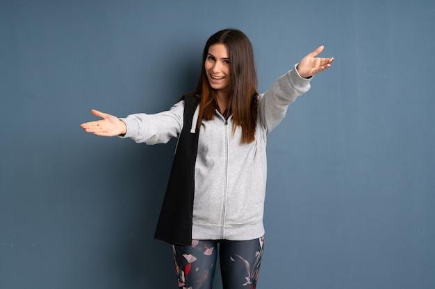 Młoda sportowa kobieta przedstawia rękę i zaprasza