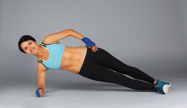 Młoda sportowa kobieta robi bocznej desce przy szarością