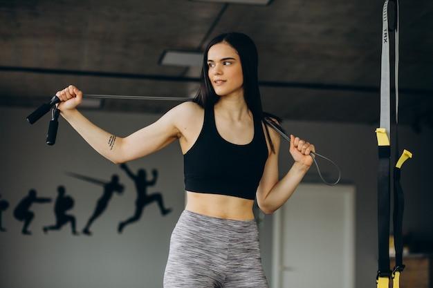 Młoda sportowa kobieta trenuje na siłowni