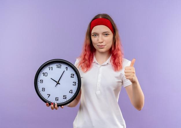 Młoda sportowa kobieta trzyma zegar ścienny pokazując kciuki do góry uśmiechnięty stojący nad fioletową ścianą