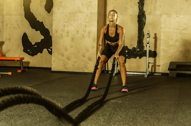 Młoda sportowa kobieta w odzieży sportowej trenuje z liną bojową w siłowni. trening funkcjonalny. koncepcja zdrowego stylu życia