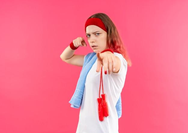 Młoda sportowa kobieta w opasce z ręcznikiem na ramieniu, wskazując palcem na aparat z poważną twarzą stojącą nad różową ścianą
