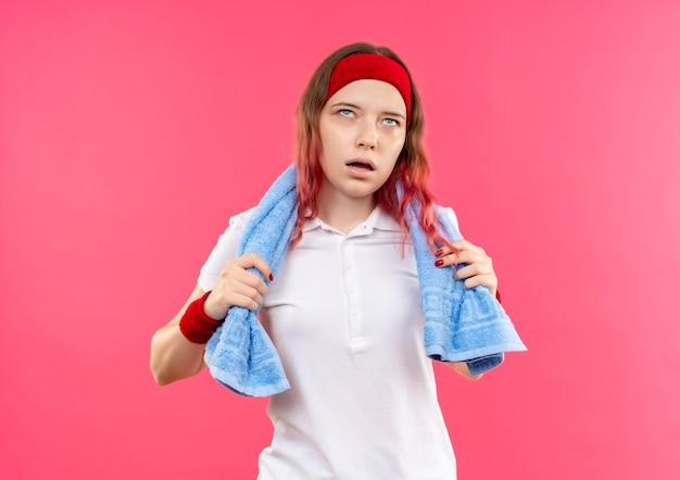 Młoda sportowa kobieta w opasce z ręcznikiem na szyi, wyglądająca na zmęczoną i wyczerpaną stojącą nad różową ścianą