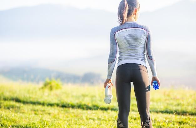 Młoda sportowa kobieta w sportowej odwrócona do tyłu. sportsmenka z butelką wody słuchawki i smartphone.