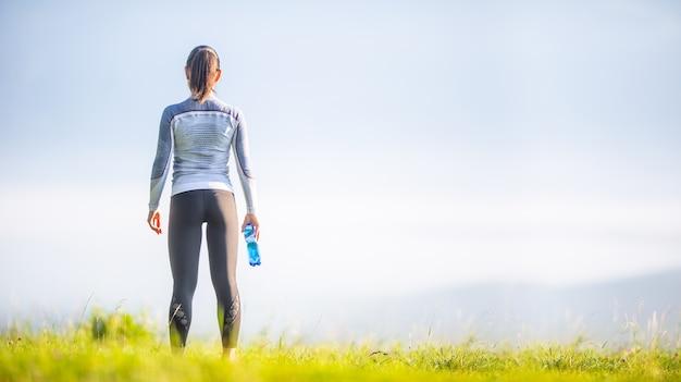 Młoda sportowa kobieta w sportowej odwrócona do tyłu. sportsmenka z butelką wody.