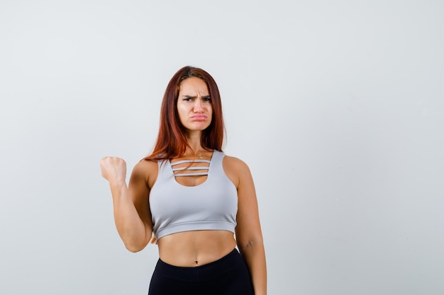 Młoda sportowa kobieta w szarym topie jest smutna
