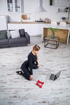 Młoda sportowa kobieta w ubraniach fitness w nowoczesnym domu, korzystając z lekcji online z witryny fitness w laptopie i wykonując trening w domu. sport w domu podczas kwarantanny