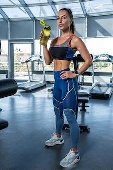 Młoda sportowa kobieta wody pitnej podczas treningu na siłowni