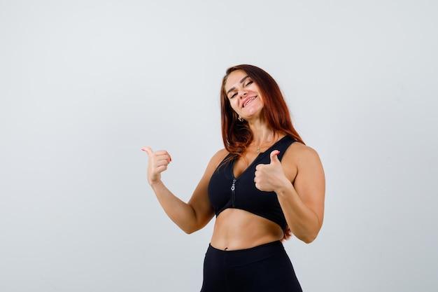 Młoda sportowa kobieta z długimi włosami pokazująca kciuk w górę