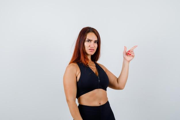 Młoda sportowa kobieta z długimi włosami w czarnym topie