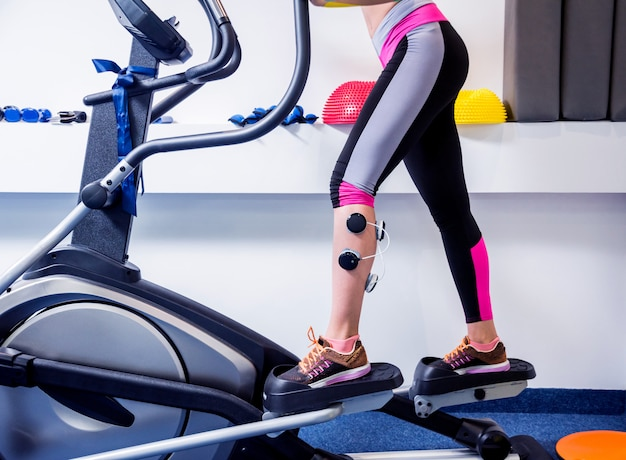 Młoda sportowa kobieta z elektrostymulatorem na mięśniach nóg.