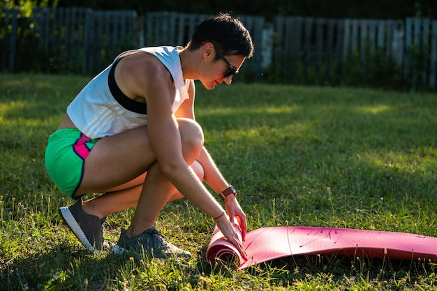 Młoda sportowa kobieta z krótkimi czarnymi włosami rozwija matę do jogi do ćwiczeń relaksacyjnych w parku na zielonej trawie, trenując na świeżym powietrzu