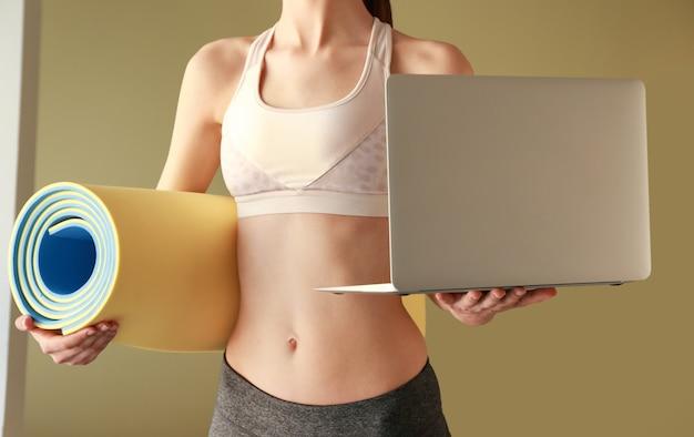 Młoda sportowa kobieta z matą do jogi i laptopem. pojęcie równowagi między odpoczynkiem a pracą