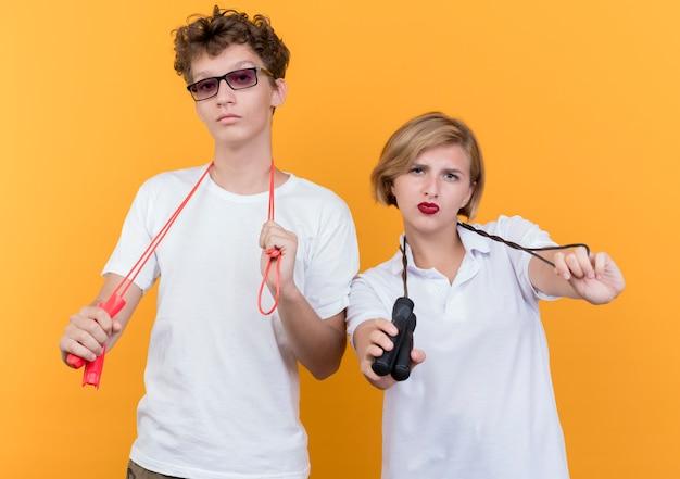 Młoda sportowa para mężczyzna i kobieta trzymając skakanki z poważnymi twarzami na pomarańczowo