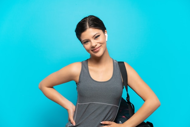 Młoda sportowa rosjanka ze sportową torbą na białym tle na niebieskim tle pozuje z rękami na biodrach i uśmiecha się
