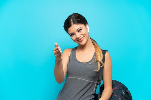 Młoda sportowa rosjanka ze sportową torbą na białym tle na niebieskim tle, ściskając ręce, aby zamknąć dobrą ofertę