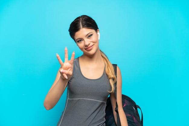 Młoda sportowa rosjanka ze sportową torbą na białym tle na niebieskim tle szczęśliwa i licząca trzy palcami