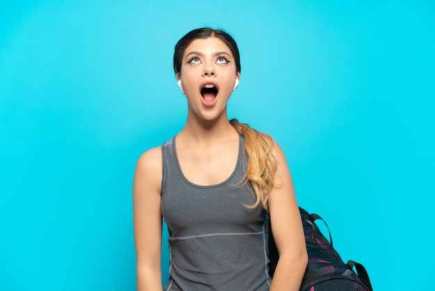 Młoda sportowa rosyjska dziewczyna ze sportową torbą na białym tle na niebieskim tle, patrząc w górę i ze zdziwionym wyrazem twarzy