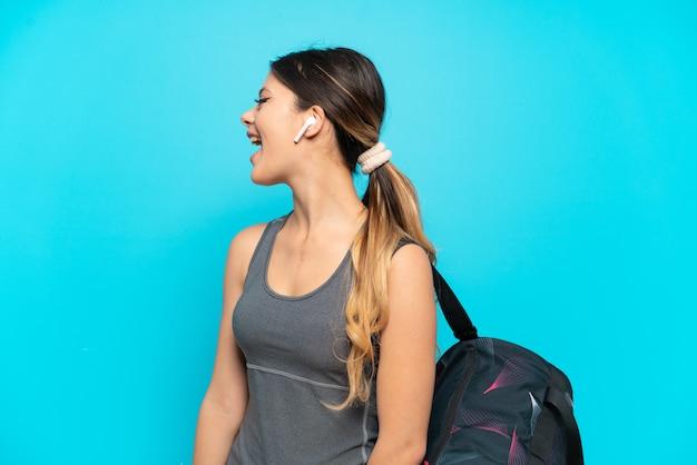 Młoda sportowa rosyjska dziewczyna ze sportową torbą na białym tle na niebieskim tle śmiejąca się w pozycji bocznej