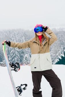 Młoda sportowa uśmiechnięta kobieta zimą z snowboard, okulary